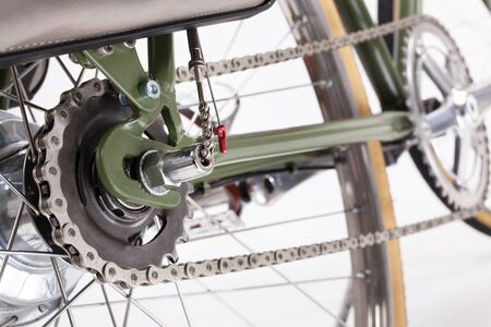 crank: Composition with back bicycle crank and chain on white background.