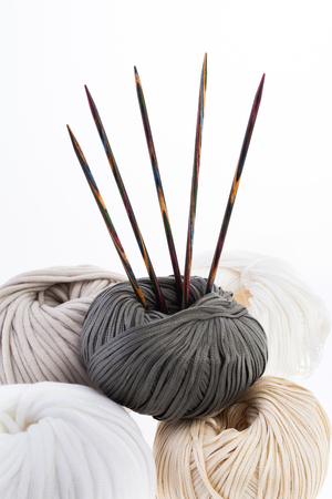 Set of pastel wool yarn wrapped in hanks and a pair of wooden double pointed knitting needles Stock Photo