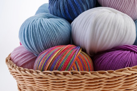 basket embroidery: Basket full of colorful wool yarn balls in it. Close-up. Stock Photo