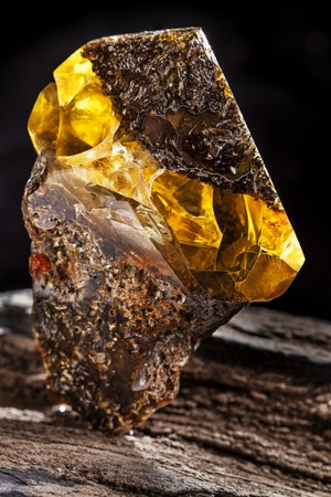 Natural amber stone. A piece of dirty amber with transparent yellow layer on piece of stoned wood.