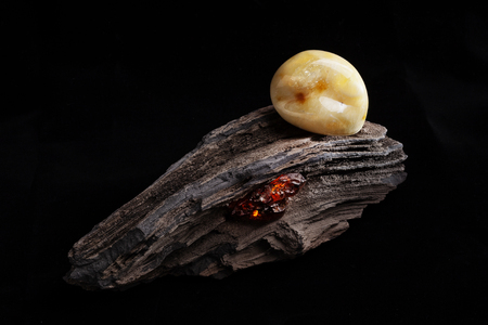 Natural amber. A piece of yellow opaque natural amber on large piece of dark stoned wood. Stock Photo