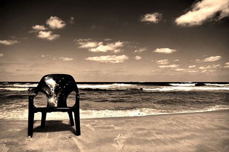 old fashion picture of a chair on the sea shore Stock Photo
