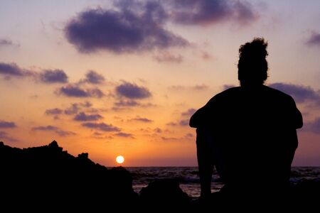 man alone sitting near the sea