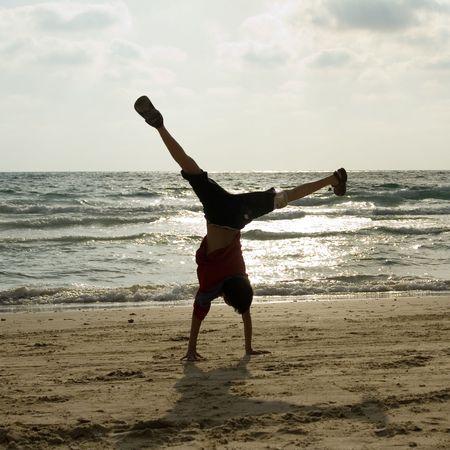 somersault: child make somersault on sand near sea