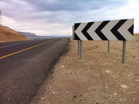empty road: Empty road near Dead sea with a turn left sign  Stock Photo
