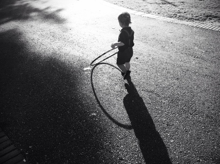 high contrast: Black and white image of child playing hoop