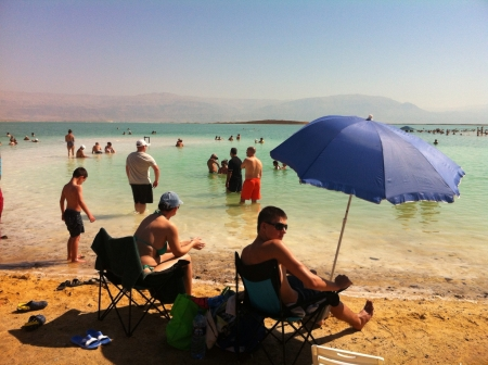 dead sea: Tourists relaxing on the sunny beach Dead Sea Israel  Stock Photo