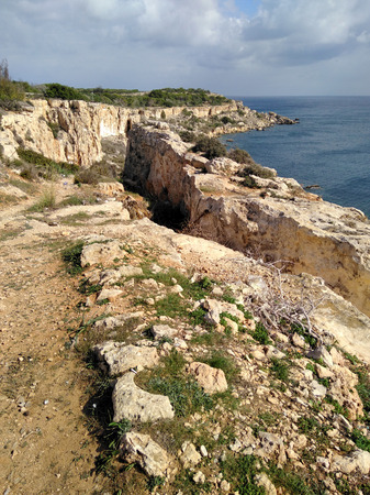 Malta seashore rock cliff view with blue sunny sky and clouds.