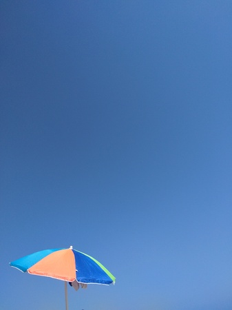 Beach tanning umbrella on a blue sky summer background with copy space for poster banner. Stockfoto