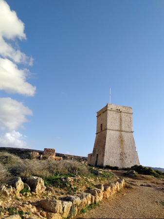 Blue sky with rocks and clouds, old guard tower on the seacost on Malta island