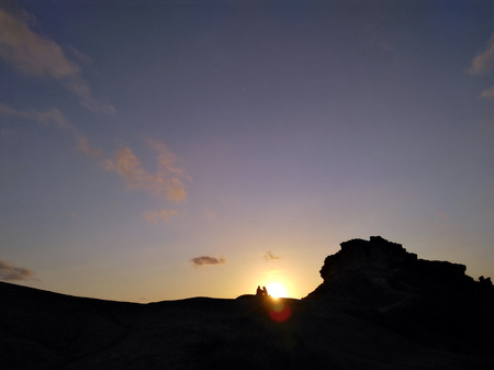 Couple - man and woman silhouette at the top of the mountain in front of sunset. Hiker rest on the rock. Background with copyspace. Symbol of romance, motivation, success, achievement