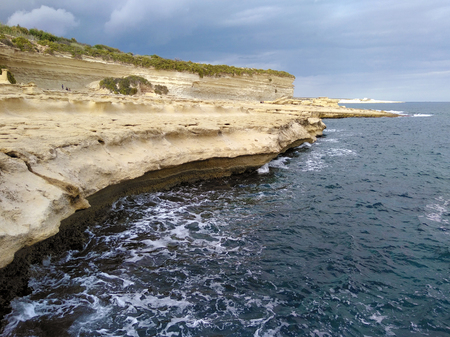 St peters pool. Malta coactline with cliff and rock with dark blue navy sea ocean and wave