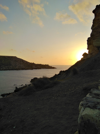 Sunset light with mountains and rocks silhouette on Malta island