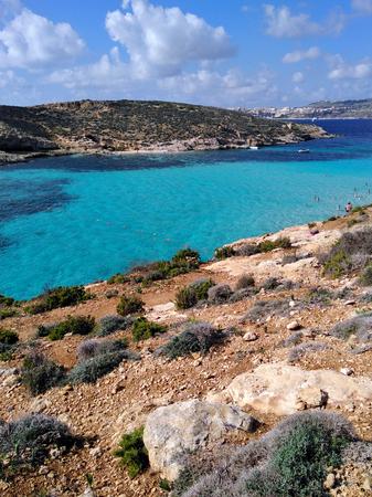 Comino island blue lagoon. Malta blue turquoise sea water beach. Rock and cliff sunny seashore. Travel mediterranean.