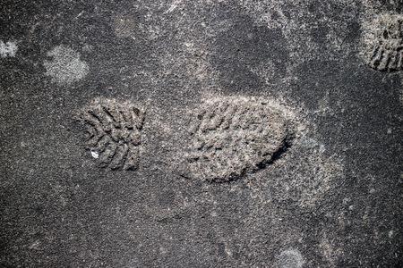 Shoeprint imprinted on the gray asphalt.
