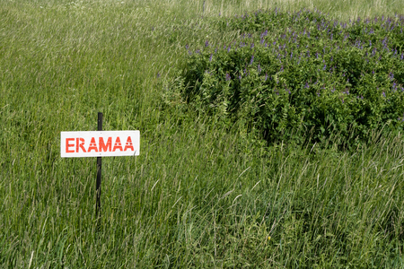 Red painted sign in Estonian language saying Private Land.