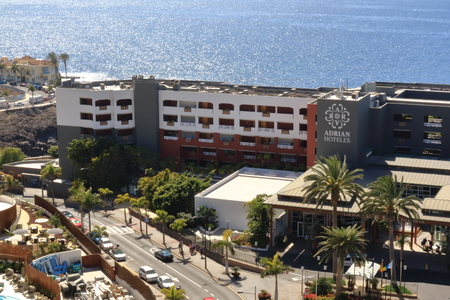 Playa Paraiso, Tenerife, Spain 02.16.2018: view to the street near Hard Rock hotel from the air, big blue swimming pool and green area around.