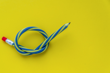 Knotted striped pencil with pink erazer lying on yellow background, concept of disappeared inspiration, fear of empty sheet of paper