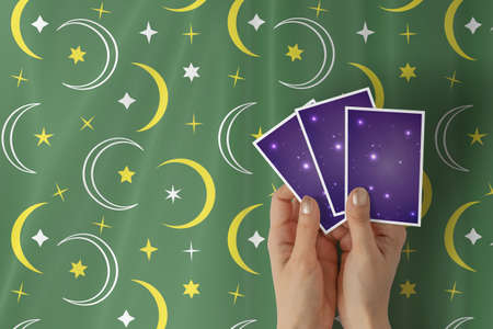 Hands of young woman with golden nail polish holding three tarot or oracle cards, on a green stars and crescent pattern table cloth. 写真素材