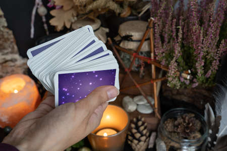 Woman hand is holding deck of tarot or oracle cards performing fortunetelling.
