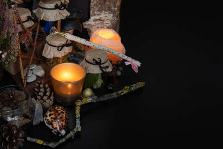 Black table with magic items, candles, pentacle star, magic wand. Space for the text.