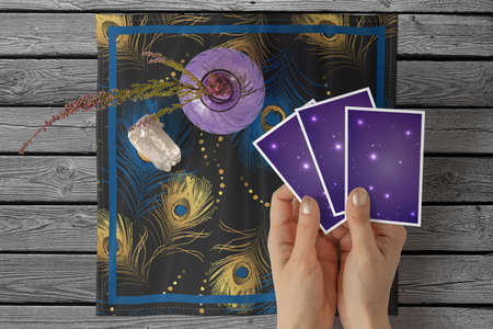 Hands of young woman with golden nail polish holding three tarot or oracle cards, on a black peacock feathers pattern square table cloth 写真素材