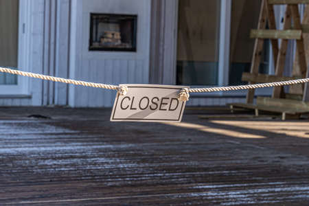 Closed sign hanging on entrance to an empty beach restaurant terrace