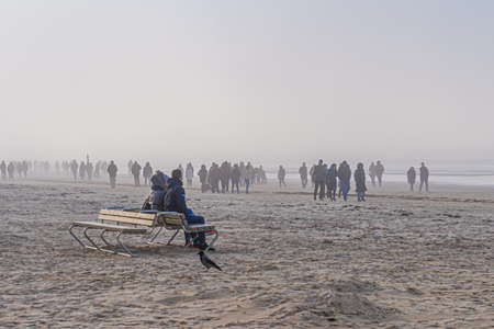 Crowd of people walking on a beach on foggy spring day