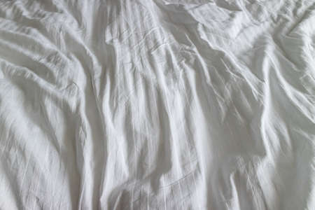 Wrinkled clean white bedsheet on a bed closeup texture