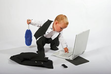 iq: Young child in suit working on a laptop computer, isolated