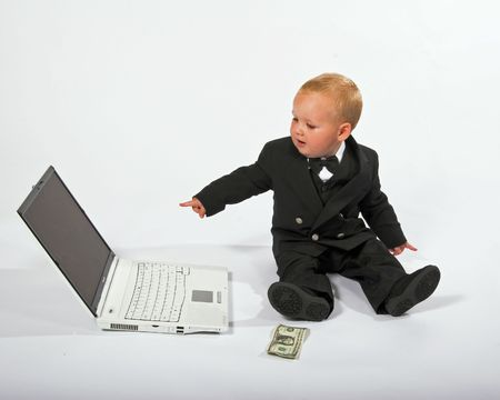 techincal: Young child in suit working on a laptop computer, isolated