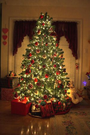 Home with lighted christmas tree, presents photo