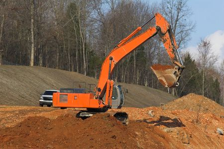 bright colored trackhoe moving dirt for new highway photo