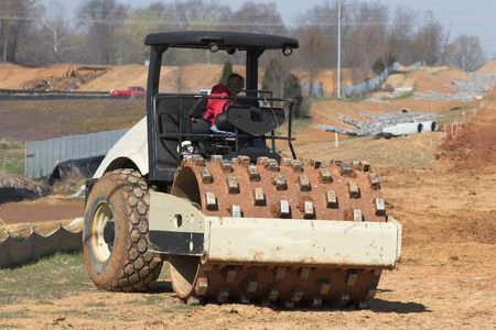 roller compactor: Large roller packing dirt for new highway being operated by woman
