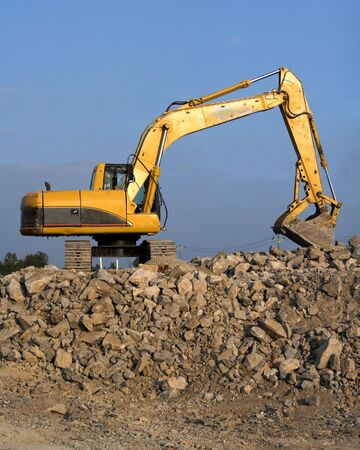 Large track hoe being used to fill dump trucks with rock to be