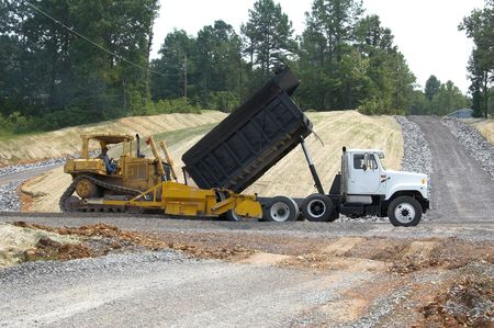dumps: Large dump truck feeding machine that packs new road base to make ready for concrete