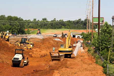 Trackhoe , bucket loader and lots of heavy equipment in ditch helping to lay drainage pipe for new highway photo