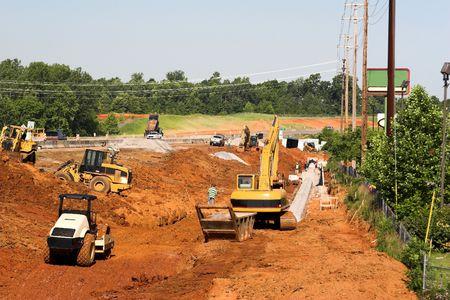riool: Trackhoe, emmer ladertype en veel zwaar materieel in de greppel te helpen leggen drainage pijp voor nieuwe snelweg Stockfoto