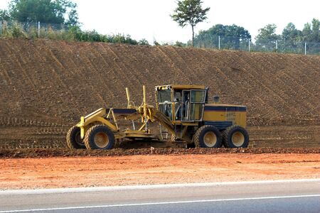 Grader  leveling dirt for new highway photo