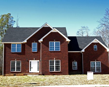 New brick home with white blank  forsale sign in front yard photo