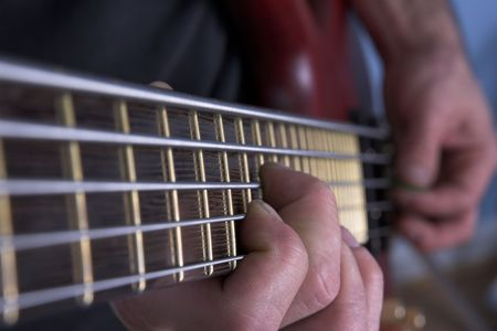 played: Closeup of five string bass guitar being played Stock Photo