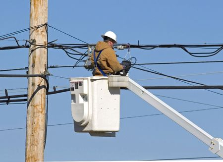 lineman: Cable technician working on communication lines by using bucket lift truck Stock Photo