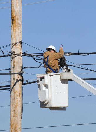 outage: Cable technician working on communication lines by using bucket lift truck Stock Photo