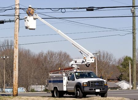 Cable technician working on communication lines by using bucket lift truck Stock Photo