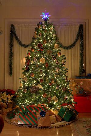 El árbol de Navidad en el hogar caliente, luces encendido, presenta debajo de árbol Foto de archivo - 668200