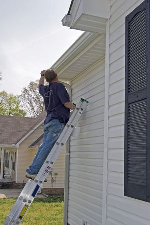 Local contractor painting outside of house, business is booming in summer months Stock Photo