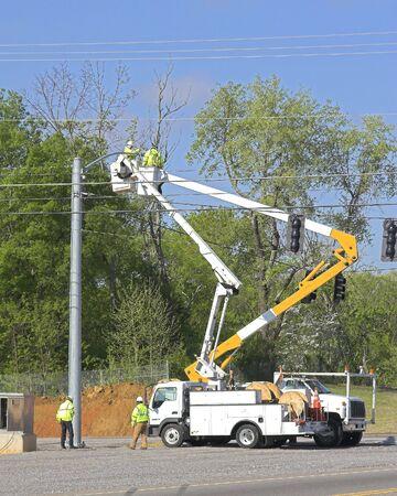 전기 회사가 교차로에서 새로운 신호등을 설치하고 있습니다.