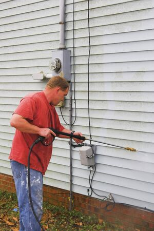 Contractor pressure washing house, removing mildew & mold from vinl siding and trim, also cleans sidewalks & driveways  Stock Photo