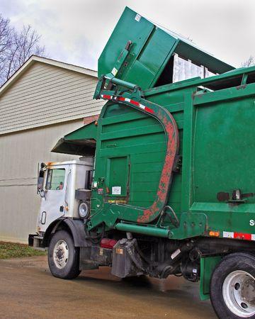 Truck pickingup dumpster full of trash Imagens