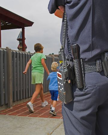 Children in play area in park well policeman watches over them